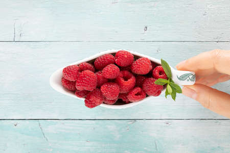 Fruity raspberries in a saucer hold by a woman hand Stok Fotoğraf