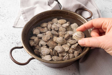 Raw clams in the water inside a copper bowl.