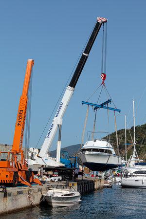 MARCIANA MARINA, ELBA ISLAND, ITALY - JUNE 22, 2012: Boat launch operations with marina crane in the small touristic port.