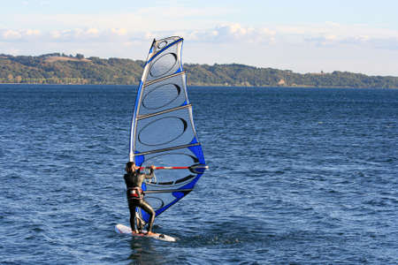 Man windsurfing on a lake in Italy