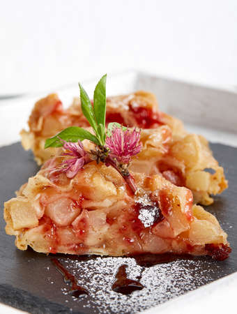 Pie strudel slices on a piece of slate decorated with freshapple flowers and leaves and icing sugar Stok Fotoğraf
