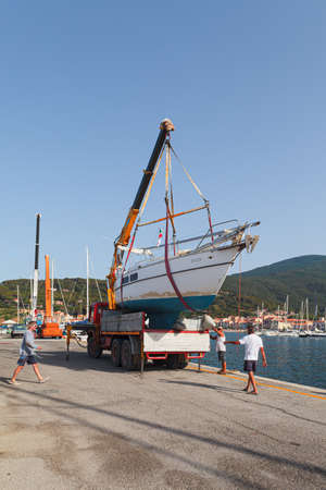 MARCIANA MARINA, ELBA ISLAND, ITALY - JUNE 22, 2012: Team of people preparing to launch a motorboat in the water.