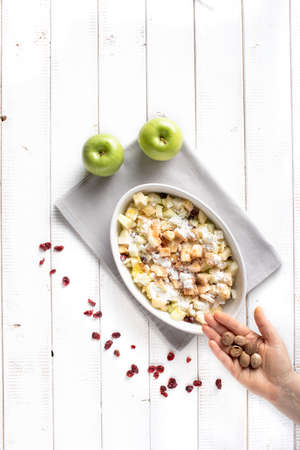Adding grated nutmeg spice  in the filling for the apple strudel consisting of apples, raisins, grated lemon zest, maize flour, cinnamon and vanilla powder. Stok Fotoğraf