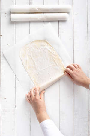Rolling phyllo dough for apple strudel in a sheet of kitchen paper