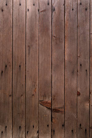 Brown wood background with vertical slats and nails.