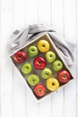 Colorful apples in a white wood tray on a white table top view