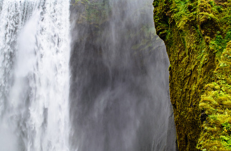 skogafoss waterfall: View of the Skogafoss waterfall, mist, and hill in Iceland Stock Photo