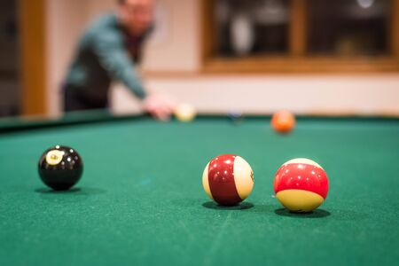 solids: A closup of several billiard balls, with the player and background balls out of focus Stock Photo