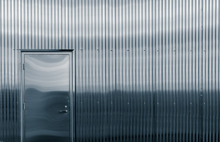 A closup of a shiny corrugated metal structure and door