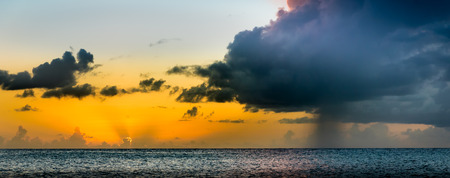 togther: Dramatic sunset off a Caribbean beach togther with a isolated raincloud