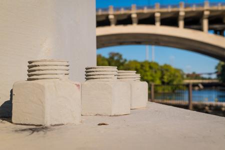 tuercas y tornillos: Grandes tuercas y tornillos de soporte un poste metálico de grandes dimensiones Foto de archivo