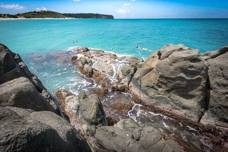 snorkelers: Caribbean beach scene with snorkelers and rocky outcrops