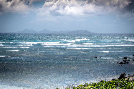 choppy: A view of a distant tropical island (St Barts) through choppy waves and threatening weather Stock Photo