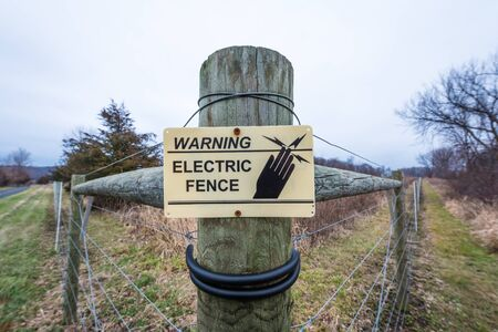 An electric fence and warning sign in a prairie-like setting Banco de Imagens