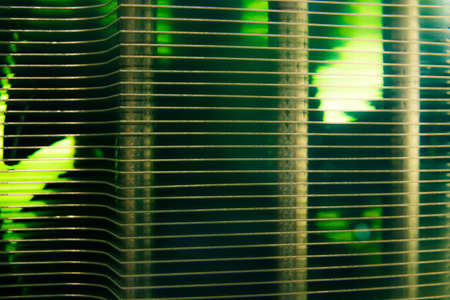 A green backlit view through the cooling fins of a computer heat sink and fan