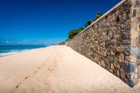 A sun-filled Caribbean beach scene with a stone wall
