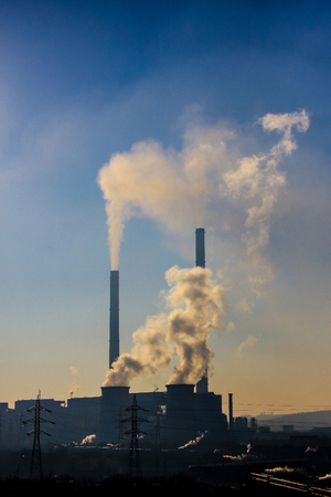 Polluting white and thick smoke coming out from four furnaces on an industrial power plant Stock fotó