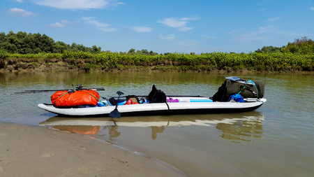 A double person inflatable kayak equipped for touring in a sunny summer day on a small canal