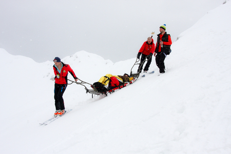 Oslea HiRide 2015 - Team of three mountain ski rescuers transporting an accident victim on a sledge stretcher