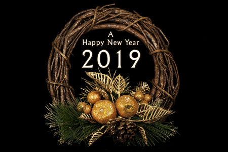 Happy new year 2019 on Round shaped wood wicker with a base from natural pine leafs and some shining fruits gilded in golden polish