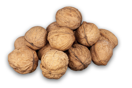A stack of hard shells of walnuts piled together and isolated on white background