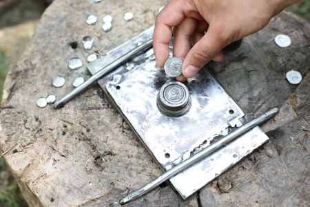 Roman Minted coin held in hand after hammering process of minting - historical reconstruction