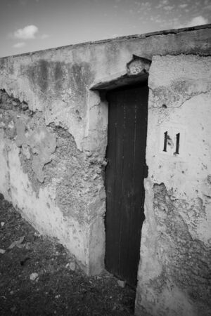 colom: A crumbling wall surrounds a door that seems to lead nowhere at Porto Colom harbor.