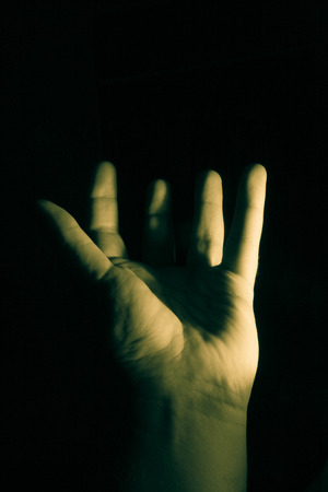 grasp: A low key photo of an open hand with upstretched fingers.