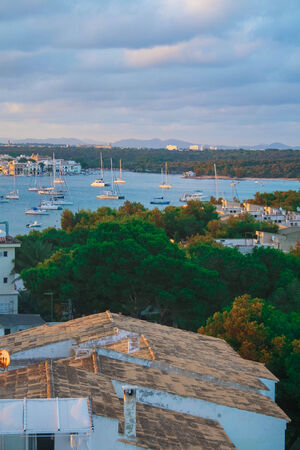 colom: A forested harbour at sunset at Porto Colom, Majorca.