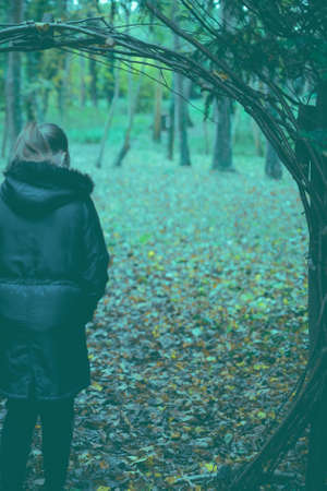 Girl Standing In Tree Arch On Autumn Day With Back To Camera