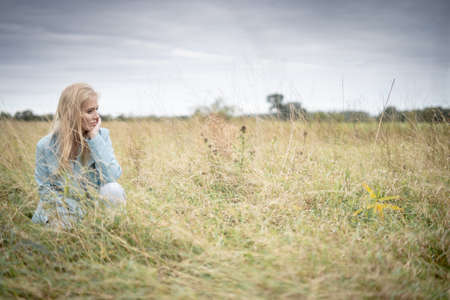 Young Woman In Long Grass In A Field Looking Away
