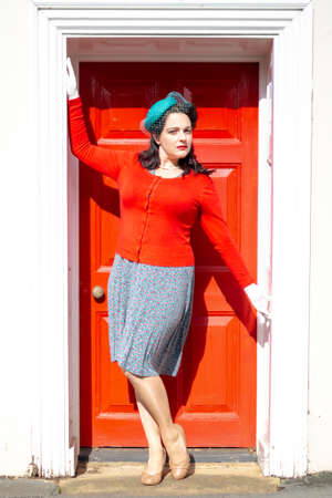 Beautiful young woman posing in vintage 1940s clothes, posing against red door with white frame