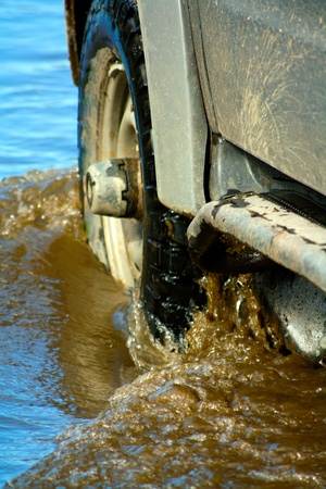 Close up photography of wheel of car moving cross river