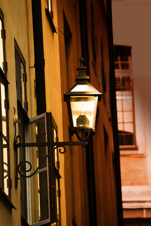 Old metal streetlamp with economical modern bulb on the yellow wall Stock Photo