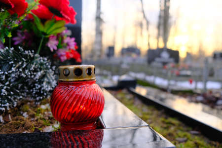 Red glass candle lattern on the grave.