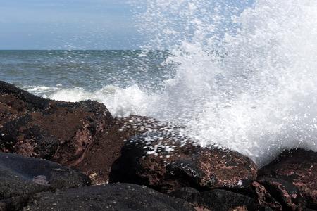 Waves splashing towards a rock Archivio Fotografico