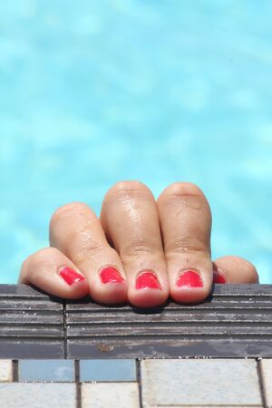 Actual shot is of a girls hand and red painted finger nails in a swimming pool