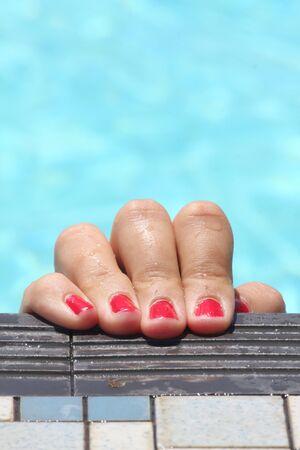 Tatsächliche Aufnahme ist von einer Mädchenhand und rot lackierten Fingernägeln in einem Schwimmbad