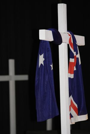 The Austrlian Flag symbolically draped over a white cross with dark backgroung.