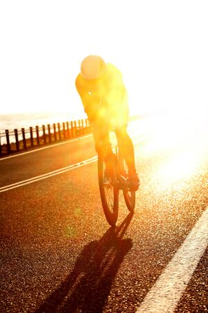 Stunning early morning shot of a triathlete riding their bike bicycle on the open road Banco de Imagens