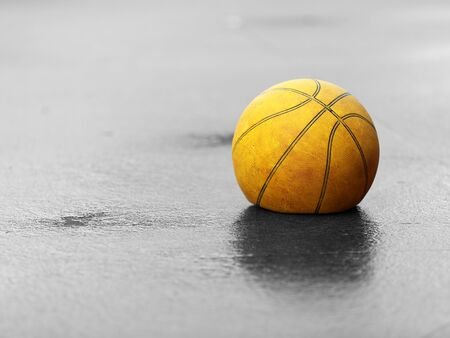 Black and white bw with single isolated colour yellow feature old used basketball. Flat deflated and let down.