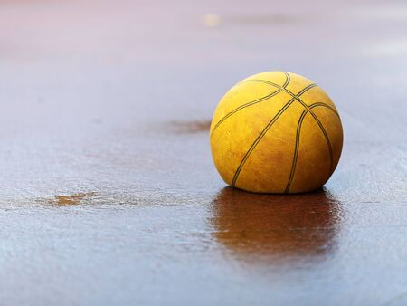 A flat deflated old tired yellow basket ball on wet concrete ground. Concept for feeling flat, bad poor rainy weather, tired, sick or need help.