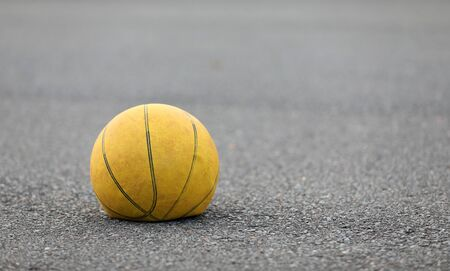 Left hand focus, old tired deflated let down yellow basketball on a road surafce concept. needs air, worn out spent and discarded sport equipment.