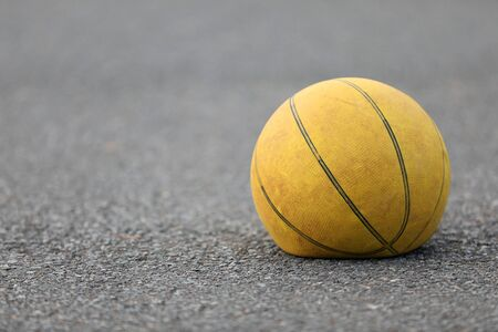 Right hand focus, close up of old tired deflated let down yellow basketball on a road surafce concept. needs air, worn out spent and discarded sport equipment.
