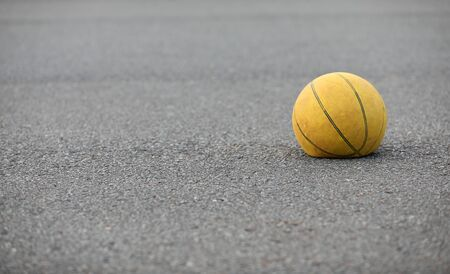 Right hand focus, wiede view of old tired deflated let down yellow basketball on a road surafce concept. needs air, worn out spent and discarded sport equipment.