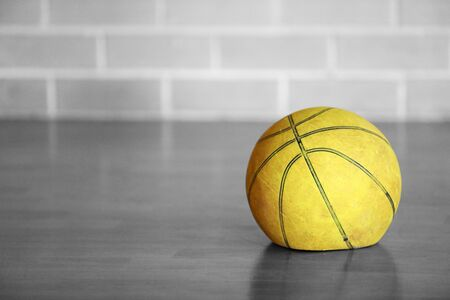 Old tired worn out flat deflated yellow basketball indoors on wooden floor with brick background. Lack lustre performance. Black and white isolated colour