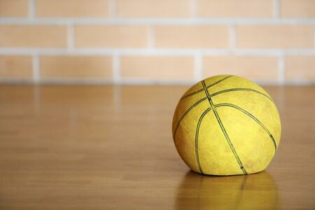 Old tired worn out flat deflated yellow basketball indoors on wooden floor with brick background. Lack lustre performance