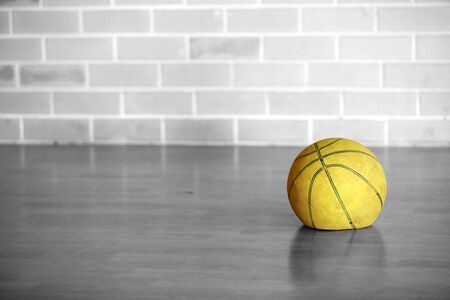 Black and white isolated colour yellow old tired flat let down deflated basketball. Worn out spent no energy used sporting equipment. life.