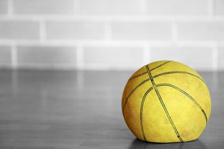 Close up black and white isolated colour color old tired let down deflated worn out spent basketball on a wooden court with blurred brick background. Used sporting equipment, broken, flat, no energy. Banco de Imagens