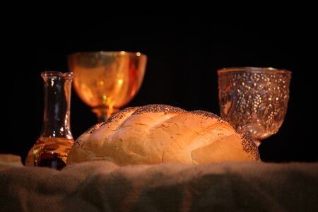 Bread wine and holy blessed water on a table for an easter liturgy mass with beautiful warm lighting. Image of christianity, religion and traditional spiritual concepts. Leven bread